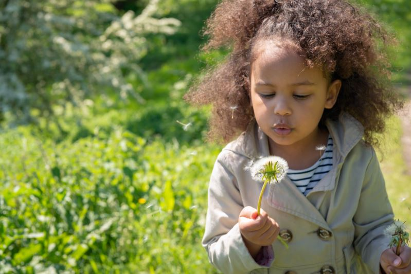 child in nature with a flower in her hands