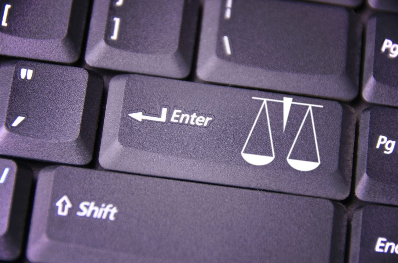 picture 'the digital court of justice': close-up of a keyboard enter key depicting a set of scales